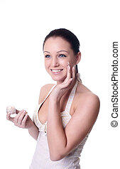 young woman applying creme on face