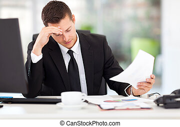 businessman reading documents - stressed businessman reading...