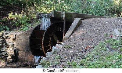 waterwheel - vintage steel waterwheel turning at the end of...