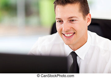 businessman looking at computer screen - handsome...