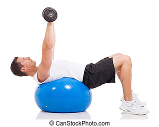 young man exercising using a fitness ball and dumbbells