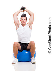 young man exercising with dumbbells on a fitness ball on...
