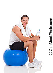 young man sitting on fitness ball after exercise