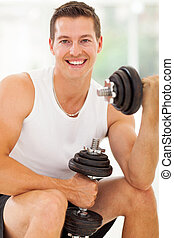 cheerful young man working out with dumbbells