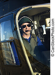 Male pilot in helicopter. - Portrait of helicopter pilot...
