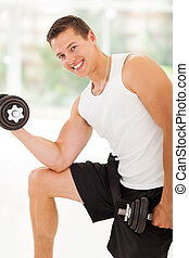 muscular man lifting weights - attractive muscular man...