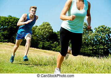 Two athletes running through meadows - Image of two athletes...