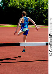 Athlete jumping over the hurdle - Back view of male athlete...