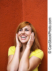 Woman covering ears - Smiling young redhead female with...