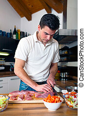 Young handsome man preparing lunch