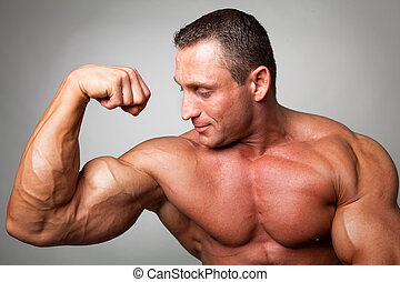 Muscular man flexing his biceps on gray background