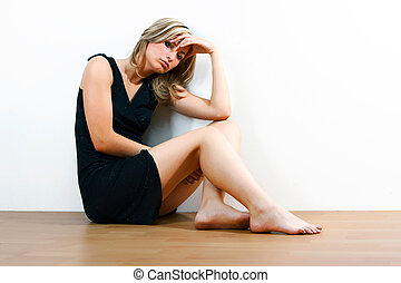 Young depressed woman sitting on floor