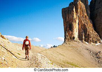 Young woman with backpack walking through rocky land - Young...