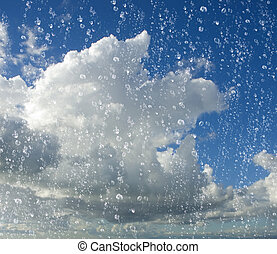 drops of rain with a cloudy blue sky in background