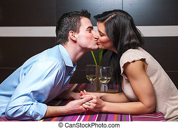 Young couple kissing in restaurant - Young couple siiting in...