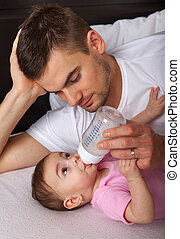 Portrait of father feeding daughter