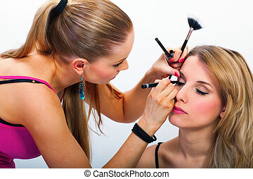 Make-up artist applying mascara on models eyelashes