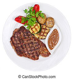Grilled steaks, baked potatoes and vegetables on white plate...