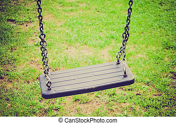 Swing retro looking - A swing suspended on chains in a...