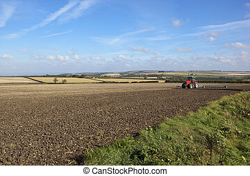 red tractor and scenery - a red tractor cultivating a field...