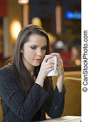 sad and sweet - young woman looking sad warming herself with...