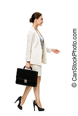 Profile of walking businesswoman with suitcase