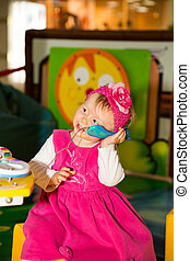 Happy child girl talking on the phone on playground. The...