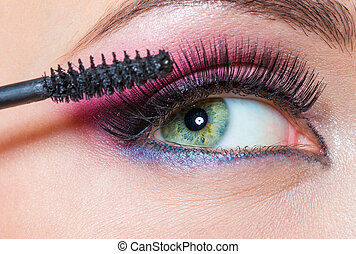 Close-up view of female eye and brush applying mascara -...
