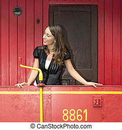 Woman Standing On A Red Caboose - Beautiful young woman...
