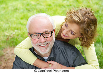 Happy older man with beautiful woman smiling outdoors -...