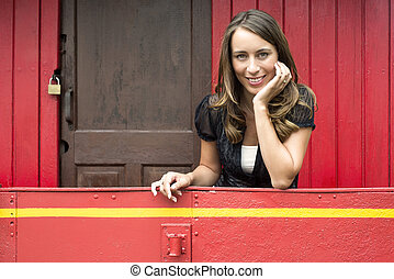 Woman Leaning On Railing In Red Caboose Car - Portrait of...