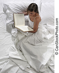 A pretty young woman reads a book in bed