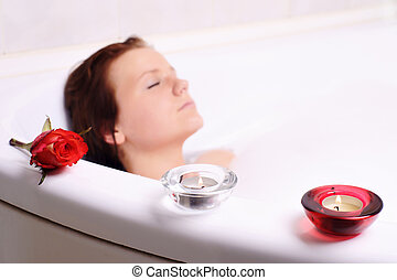 Young woman enjoys the bath-foam in the bathtub