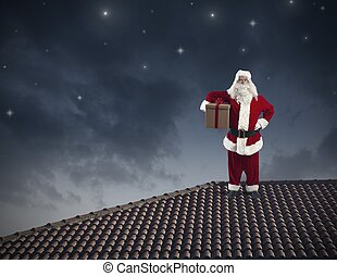 Santa Claus on a roof - Santa Claus with a big present on a...