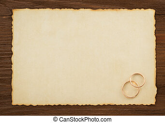 wedding ring and aged paper on wood background