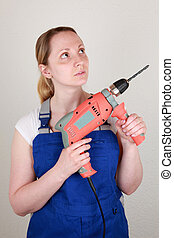 Young woman holding a drilling machine in her hands