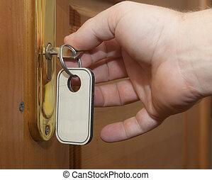 Hand with keys unlocking the front door