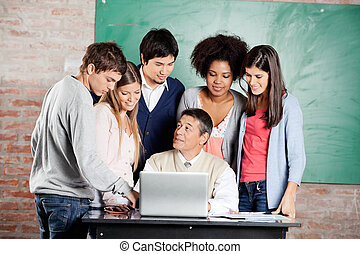 Teacher With Laptop Explaining Lesson To Students In...