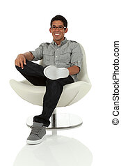 College age man relaxing in a modern chair