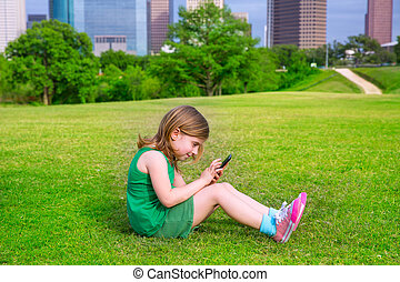 Blond kid girl playing with smartphone sitting on park lawn...