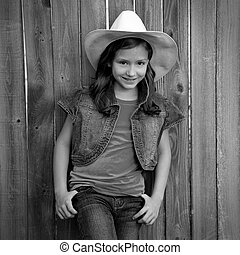 Children girl as kid cowgirl posing on wooden fence -...