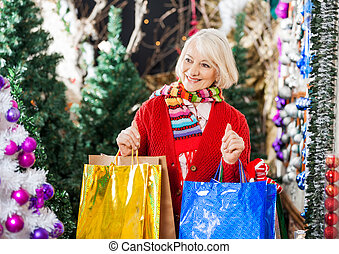 Beautiful Woman With Shopping Bags In Christmas Store -...