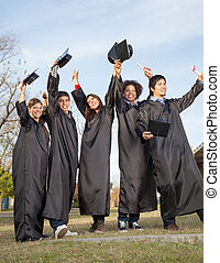 Students With Diplomas Celebrating Success On Graduation Day...