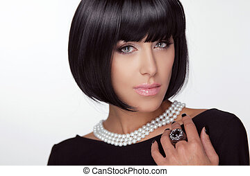 Fashion Haircut. Hairstyle. Sexy Lady. Stylish Fringe. Short Hair Style. Brunette woman with jewelry pearls