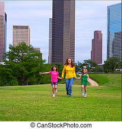 Mother and daughters walking holding hands on city skyline -...