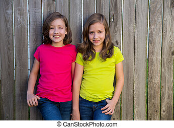 Twin sisters with different hairstyle posing on wood fence -...