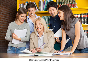 Teacher With Book Explaining Students In Library - Happy...