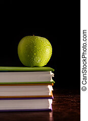 Stack books and green apple