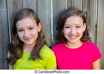 Happy twin sisters smiling on wood backyard fence - Happy...
