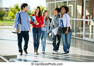 Cheerful Students Walking On Campus - Full length of...